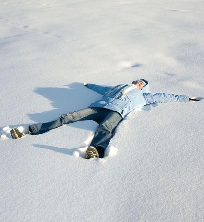 cansancio: Feliz joven tumbado en la nieve