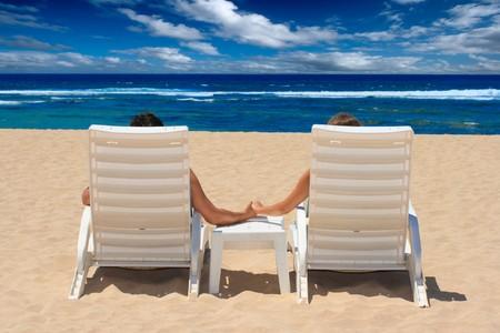 luna de miel: Joven en sillas de playa del oc�ano cerca de la mano Foto de archivo