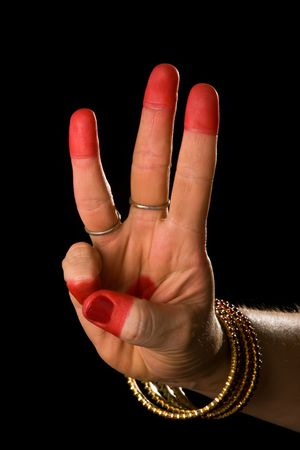 Woman hand showing Thishul hasta (hand gesture, also called mudra) (meaning trident) of indian classic dance Bharata Natyam. Also used in other indian classical dances Kuchipudi and Odissi. photo