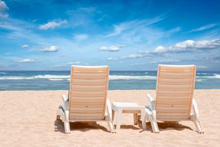 Two sun beach chairs on coast near ocean photo