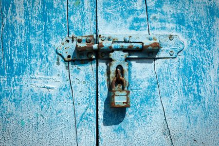 Old latch with padlock on the door photo