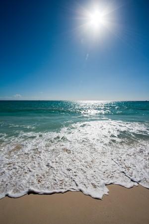 Beautiful beach, sun and waves of Caribbean Sea photo