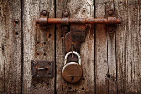 door knocker: Old latch with padlock on gatees Stock Photo