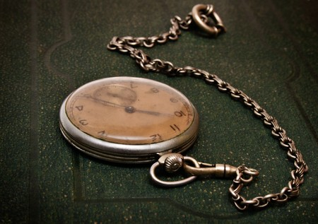 Very old clock with chain lying on rough green  surface - shallow depth of field photo