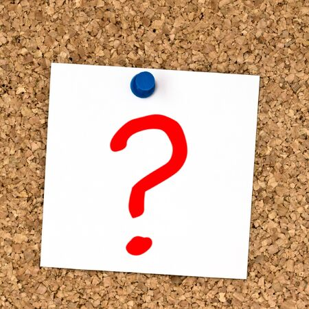 White note with question mark  pinned to cork board close up photo
