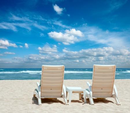 white sand beach: Two sun beach chairs on shore near ocean Stock Photo
