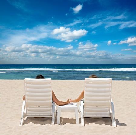 luna de miel: Pareja en la playa preside las manos de explotaci�n cerca de Oc�ano
