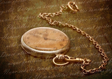 Time concept - vintage pocket watch with chain lying on rough green  surface - shallow depth of field photo