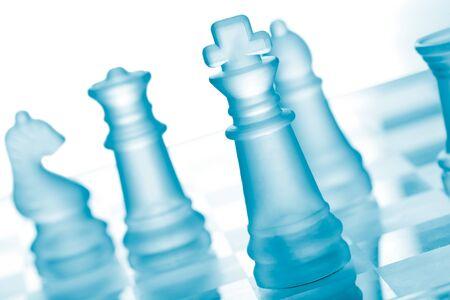 estrategia: Ajedrez de vidrio en el tablero de ajedrez Foto de archivo