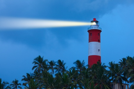 Lighthouse in night with light beam photo