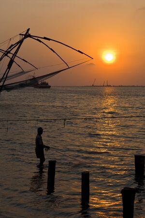medias de red: Pescador y Kochi cors�s chinos en puesta de sol. Fort Kochin, Kochi, Kerala, India Foto de archivo