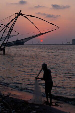 fishnets: Fisherman and Kochi chinese fishnets on sunset. Fort Kochin, Kochi, Kerala, India Stock Photo