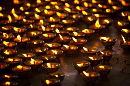 Burning candles in Buddhist temple. Tsuglagkhang complex,  McLeod Ganj, Himachal Pradesh, India photo