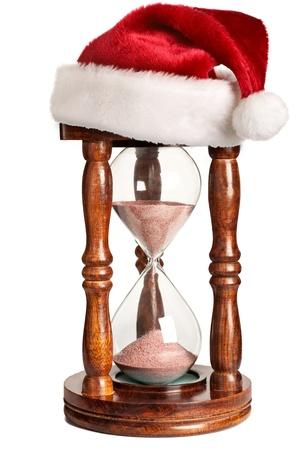 pere noel: No�l est venir concept - sablier avec chapeau de Santa Claus isol�e sur fond blanc