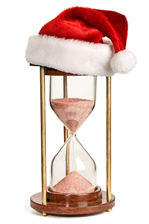 Christmas is coming concept - hourglass  with Santa Claus hat isolated on white background photo