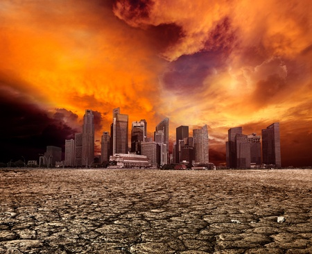 global warming: City overlooking desolate desert landscape with cracked earth