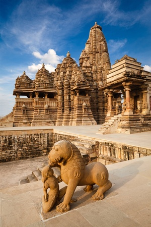 artistry: King and lion fight statue and Kandariya Mahadev temple.  Khajuraho, India