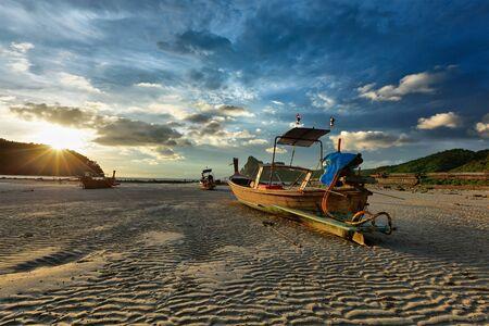 Long tail boat on beach on sunset on ebb. Thailand photo