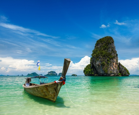 Long tail boat on tropical beach (Pranang beach) and rock, Krabi, Thailand photo