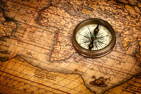 Old vintage retro compass on ancient map photo