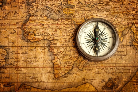 and in direction: Old vintage retro compass on ancient map