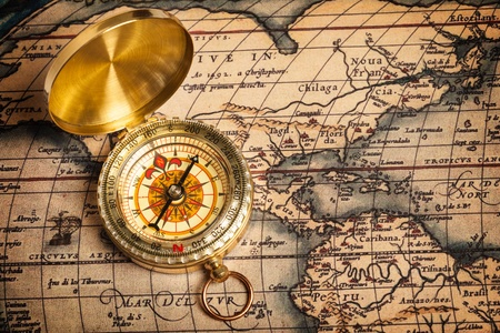 Old vintage retro golden compass on ancient map photo