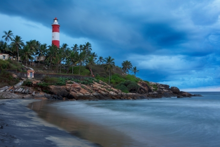 Gathering storm on beach and Kovalam (Vizhinjam) lighthouse on stormy sunset. Kerala, India photo