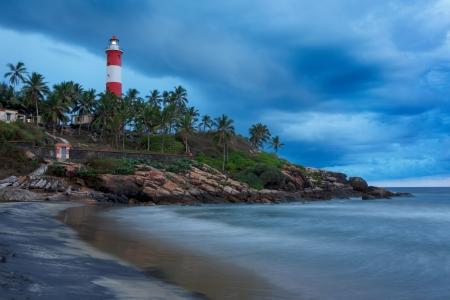 kovalam: Gathering storm on beach and Kovalam (Vizhinjam) lighthouse on stormy sunset. Kerala, India