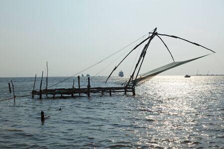 medias de red: Kochi chineese redes de pesca en la puesta del sol. Fort Kochin, Kerala, India