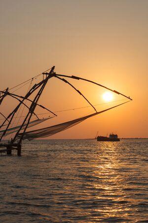 Kochi chinese fishnets on sunset and modern ship. Fort Kochin, Kochi, Kerala, India photo