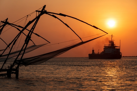Kochi chinese fishnets on sunset and modern ship. Fort Kochin, Kochi, Kerala, India photo