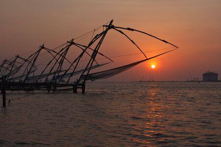 redes de pesca: Kochi chino redes de pesca en la puesta del sol. Fort Kochin, Kochi, Kerala, India