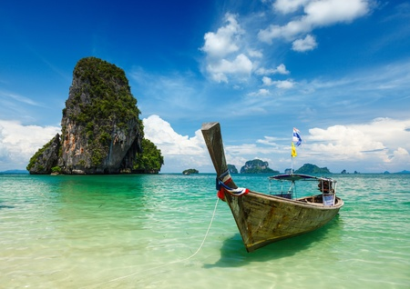 railay: Long tail boat on tropical beach (Pranang beach) and rock, Krabi, Thailand