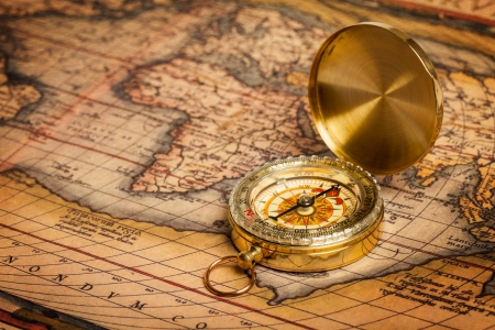 microstock: Old vintage retro golden compass on ancient map