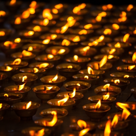 oil lamp: Burning candles in Buddhist temple. Tsuglagkhang complex,  McLeod Ganj, Himachal Pradesh, India Stock Photo