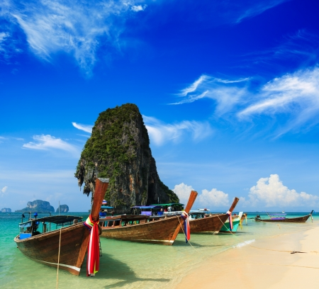 Long tail boat on tropical beach with limestone rock, Krabi, Thailand photo