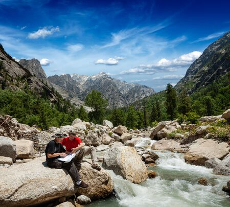 himalayas: Hiker trekkers read a trekking map on trek in Himalayas mountains. Himachal Pradesh,India Stock Photo