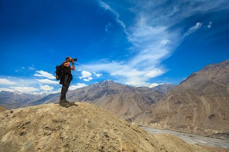 Photographer taking photos in Himalayas mountains. Spiti valley, Himachal Pradesh, India photo