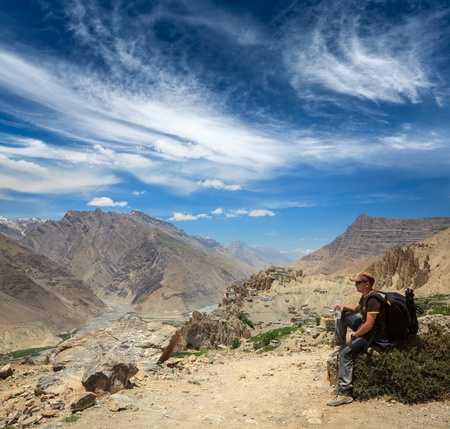 Mountaineer trekker tourist having rest and drinking water in Himalayas mountains - ecotourism concept. Spiti valley. Near Dhankar gompa (monastery), Himachal Pradesh, India photo