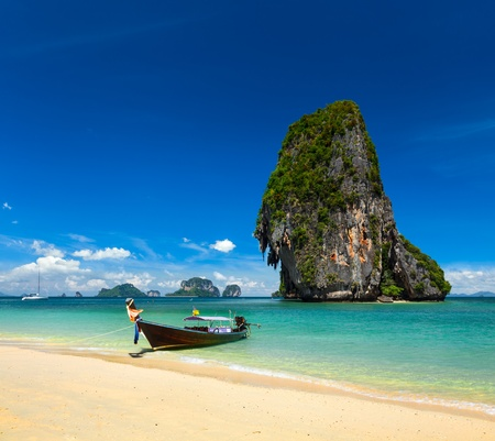 Thailand tropical vacation concept background - Long tail boat on tropical beach with limestone rock, Krabi, Thailand photo