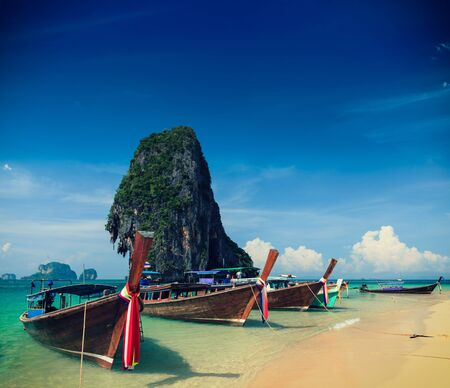 Holiday vacation concept background - Long tail boat on tropical beach with limestone rock, Krabi, Thailand photo
