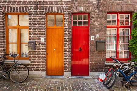 brugge: Doors of old houses and bicycles in european city. Bruges (Brugge), Belgium