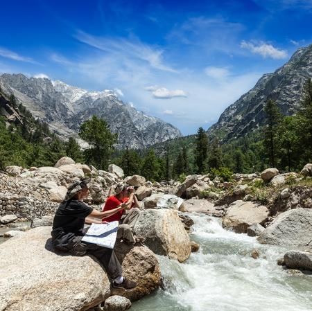ecotourism: Hiker trekkers read a trekking map on trek in Himalayas mountains  Himachal Pradesh,India Stock Photo