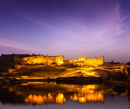 Amer Fort (Amber Fort) illuminated at night - one of principal attractions in Jaipur, Rajastan, India refelcting in Maota lake in twilight Stock Photo