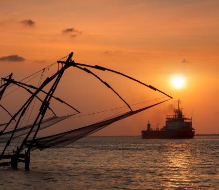 india fisherman: Kochi chinese fishnets on sunset and modern ship  Fort Kochin, Kochi, Kerala, India