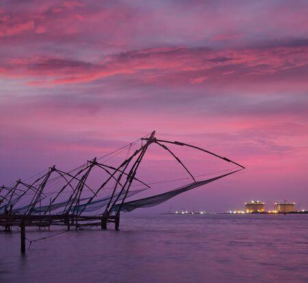 medias de red: Kochi chino redes de pesca en la puesta del sol Fort Kochin, Kochi, Kerala, India