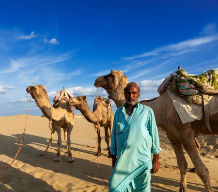 travelled: Rajasthan travel background - Indian man cameleer  camel driver  portrait with camels in dunes of Thar desert  Jaisalmer, Rajasthan, India