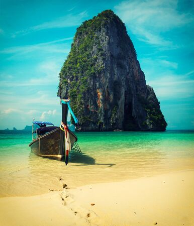 Long tail boat on tropical beach with limestone rock, Krabi, Thailand  Cross process vintage style photo