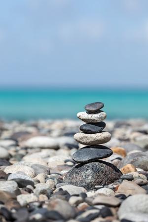 Zen meditation background -  balanced stones stack close up on sea beach photo