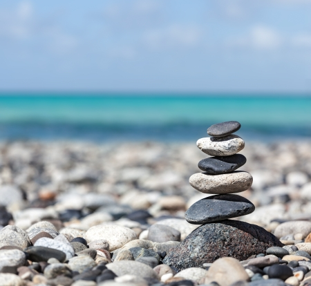 Zen meditation background -  balanced stones stack close up on sea beach photo